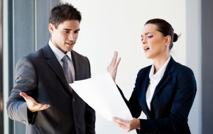 two young colleagues arguing over paperwork in office